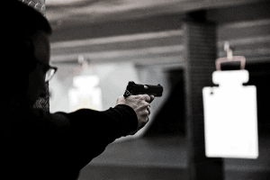 man aiming pistol down gun range