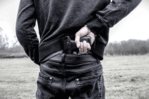 man pulling pistol from back waistband