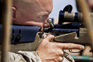 man zoomed in on rifle sniper scope
